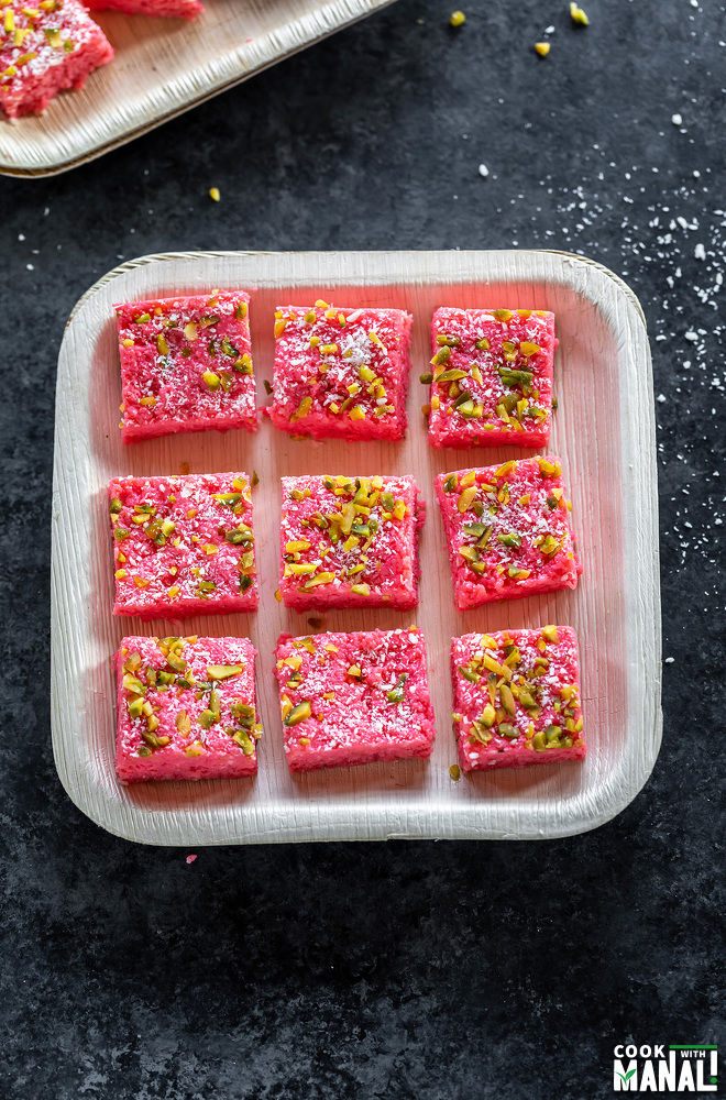 9 pieces of coconut rose kalakand placed in a plate and garnished with pistachios