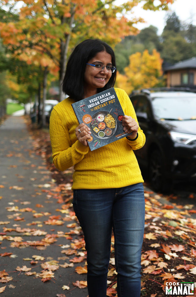 manali holding a copy of her cookbook