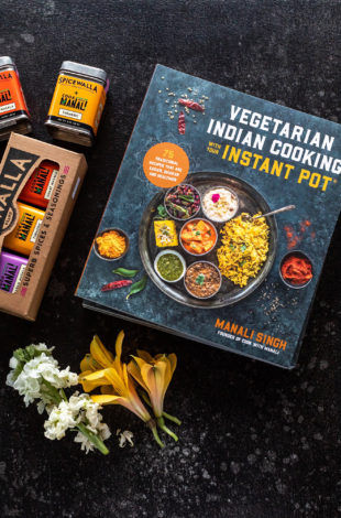 photo of vegetarian indian cooking with your instant pot cookbook along with a spice box and some flowers