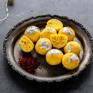 kesar malai ladoo on a silver plate with saffron strands placed on the side