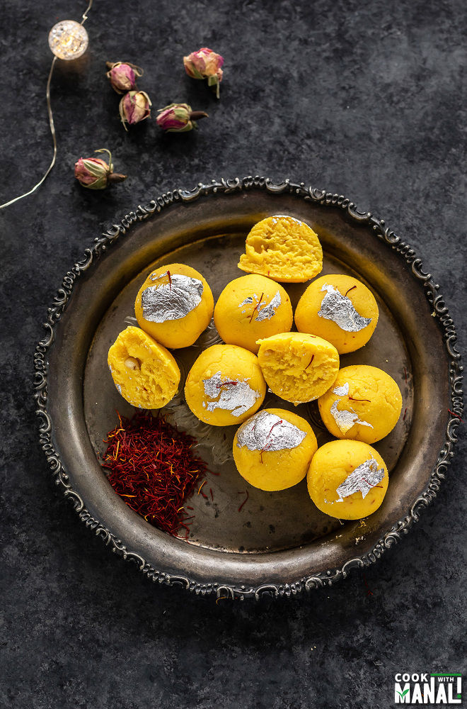 overhead shot of kesar malai ladoo arranged on a silver plate with saffron strands placed on the sides