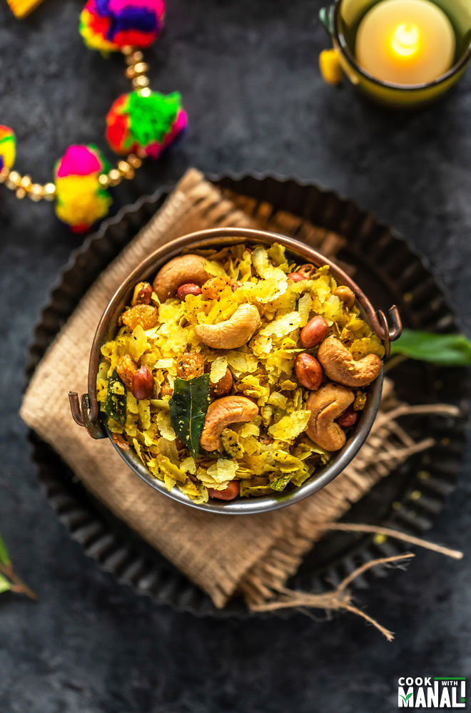 overhead shot of poha chivda served in a copper balti dish