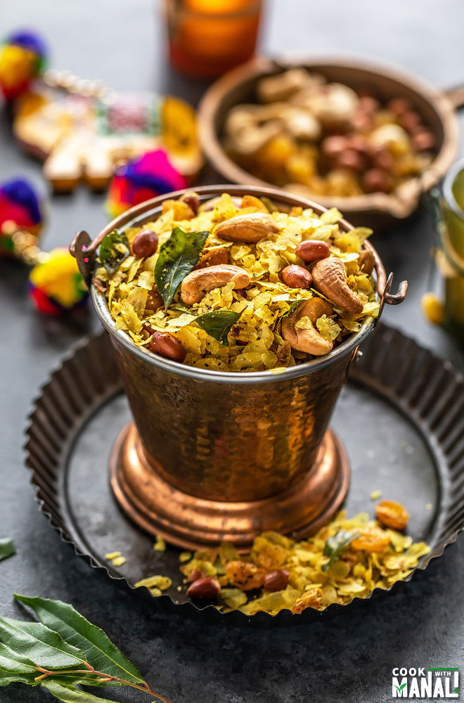 poha chivda served in a copper balti dish with decoration items and candles in the background
