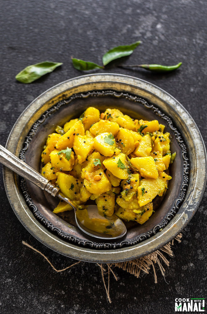 potato masala served in a rustic silver plate along with a spoon and few curry leaves scattered in the background