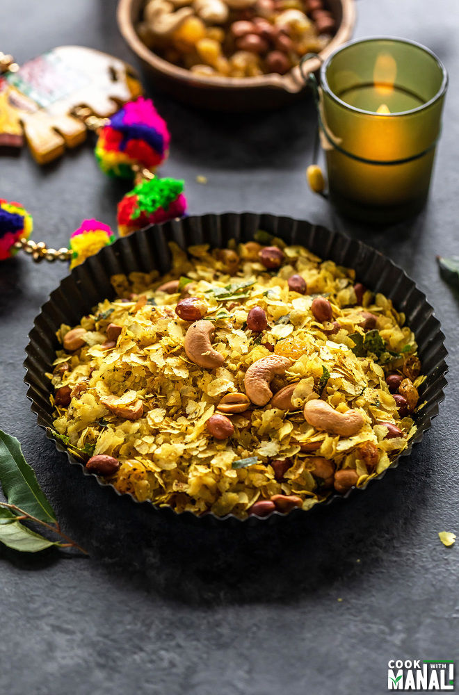 roasted poha chivda served in black rimmed plate with a candle lit in the background and some curry leaves on the side