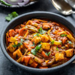 vegetable jalfrezi served in a black bowl with naan placed in the background along with some onion slices