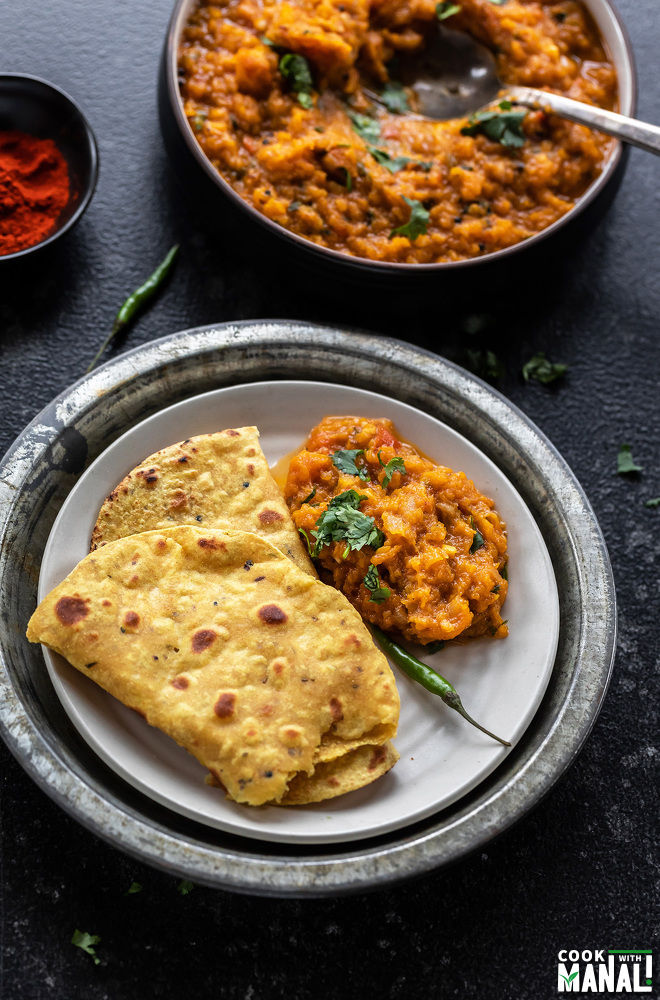 butternut squash bharta served with flatbread in a plate with a green chili placed on the side