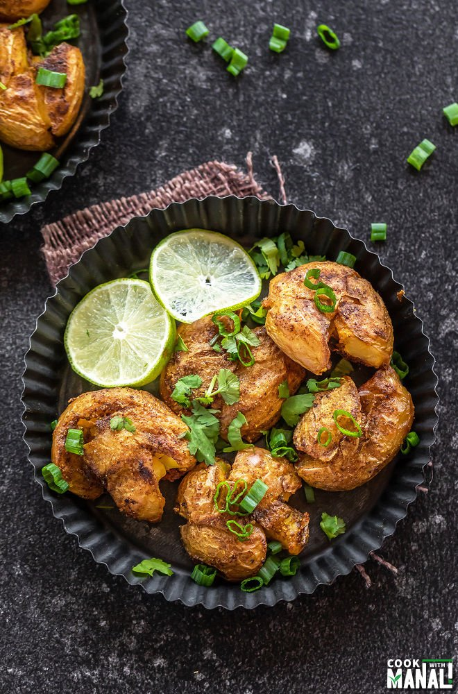 smashed potatoes served in a rimmed rustic plate with lime slices