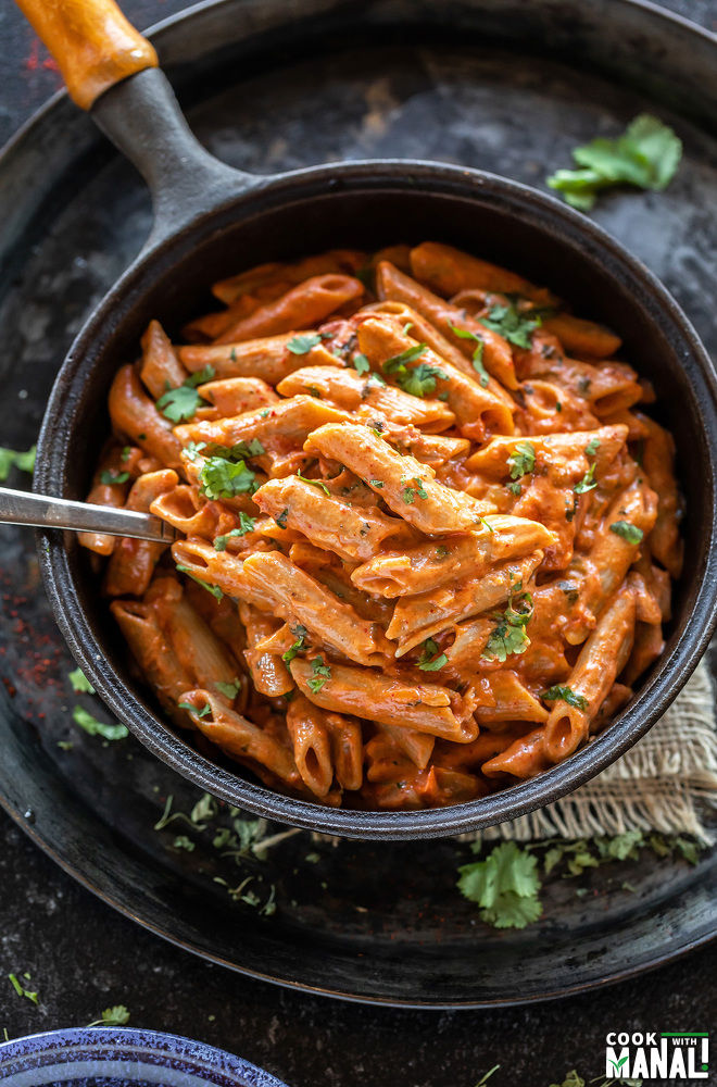 creamy makhani pasta in a skillet with a spoon