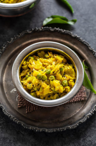 instant pot patta gobhi matar served in a small copper bowl and some curry leaves placed in the background