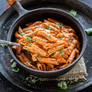 makhani pasta served in a black skillet with a spoon