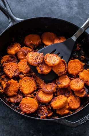 cast iron skillet with maple chili glazed sweet potatoes arranged in it