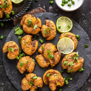 masala smashed potatoes served on a circular cheese board with lime wedges placed on the side. There's also a white color dip in a bowl in the background