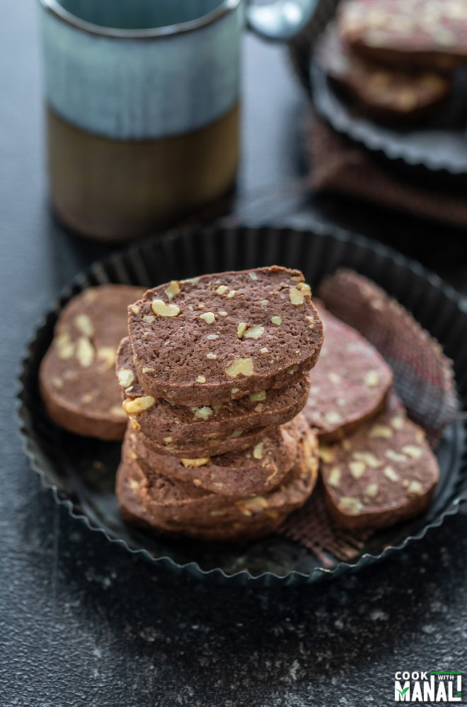 stack of chocolate walnut cookies placed in a rimmed black plate and a cup of coffee in the background
