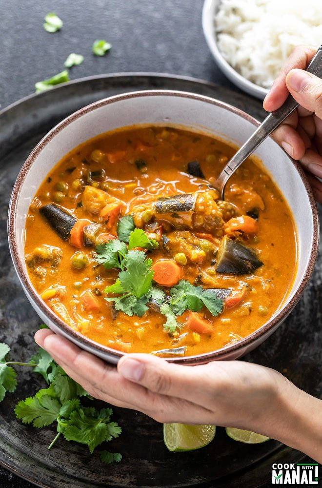 pair of hand holding a bowl of eggplant carrot curry
