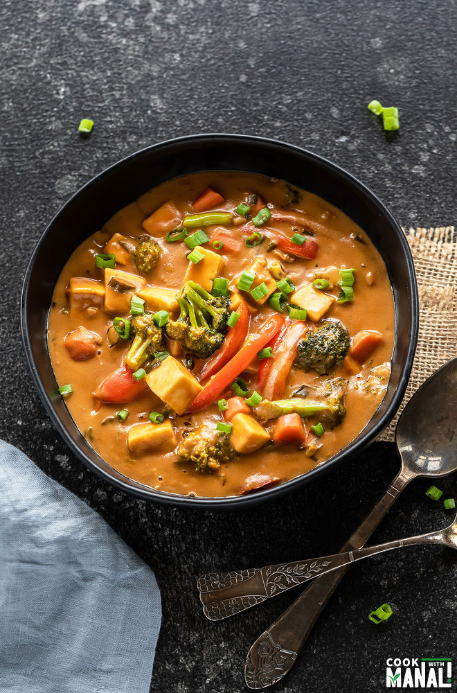 bowl full of veggies in peanut sauce with a blue color napkin placed on the side