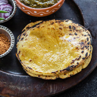 stack of makki ki roti on a plate with a bowl of saag and bowl of powdered jaggery and sliced onions on the sides