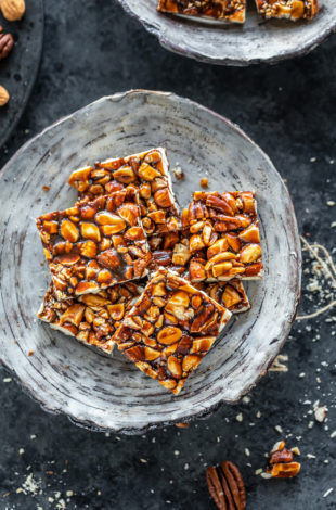 mixed nuts chikki in a white bowl and few nuts scattered on the sides and background