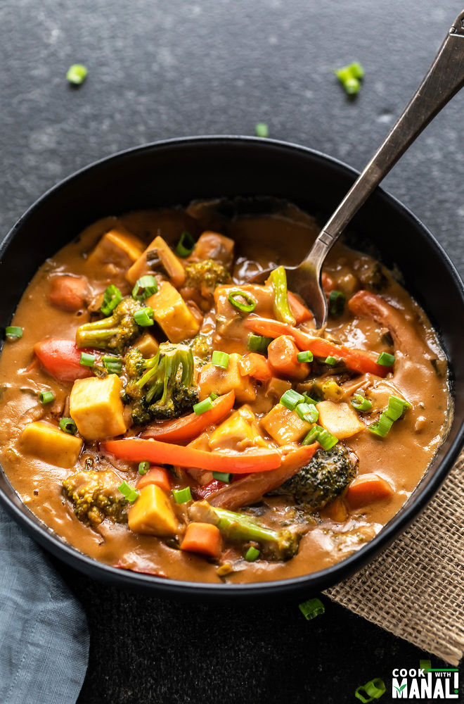 spoon digging into a black bowl of veggies in peanut sauce
