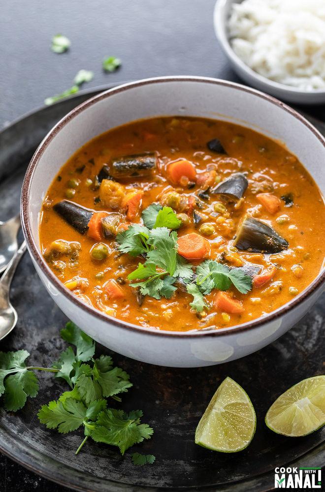 bowl of eggplant carrot curry garnished with cilantro and two lime wedges placed on the side