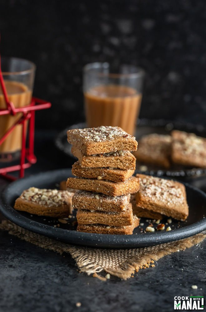 stack of almond jaggery cookies placed in a silver plate with glasses of chai in the background and on the side