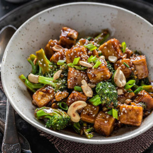 tofu broccoli stir-fry served in a white bowl with a spoon placed on the side
