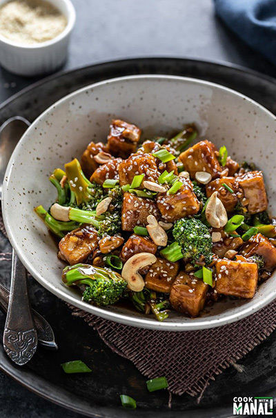 bowl of tofu and broccoli stir fry garnished with cashews and sesame seeds
