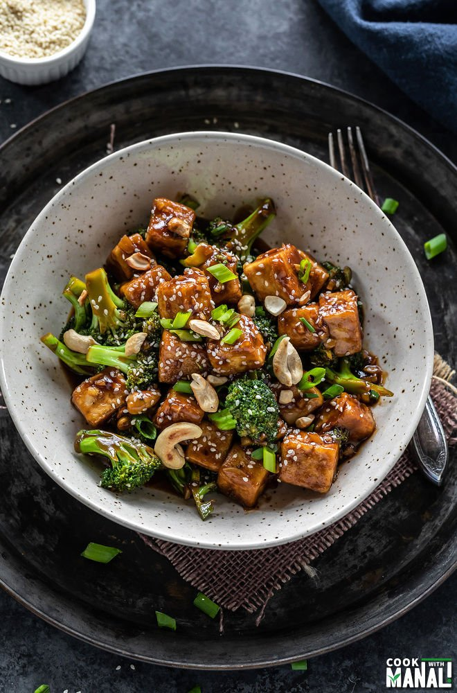 tofu broccoli stir-fry served in a white bowl with a fork placed on the side