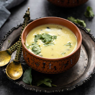 gujarati kadhi served in a ceramic bowl and garnished with cilantro with another bowl of rice in the background