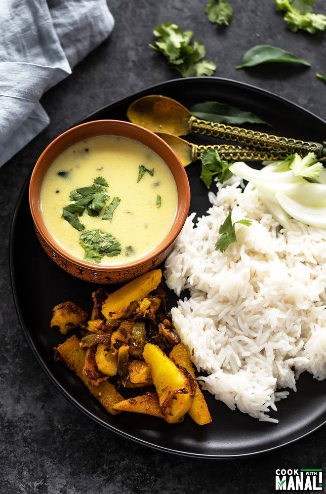 a black plate with a bowl of gujarati kadhi, boiled rice and spiced potatoes