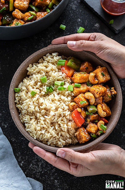 pair of hand holding a bowl of honey cashew tofu served with brown rice