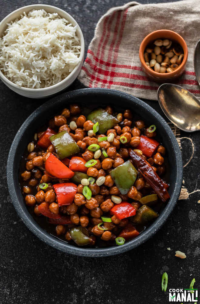 kung pao chickpeas in a black bowl garnished with green onion with a bowl of rice in the background and a spoon on the side