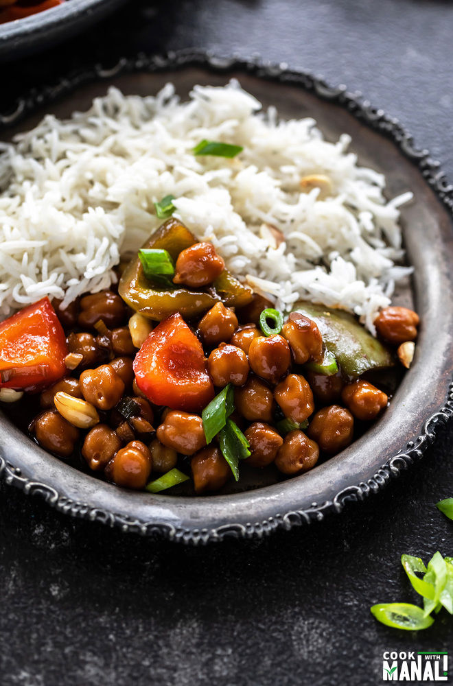 picture of kung pao chickpeas served along with white rice in a rimmed silver plate
