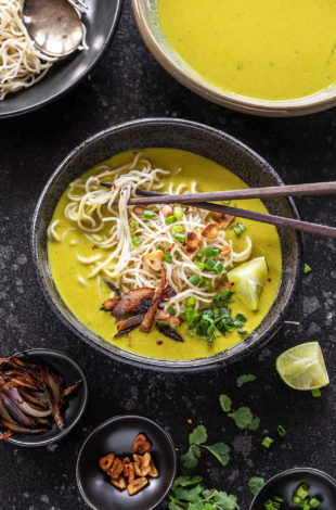 bowl of burmese khow suey with chopsticks and garnished with cilantro, lime wedge