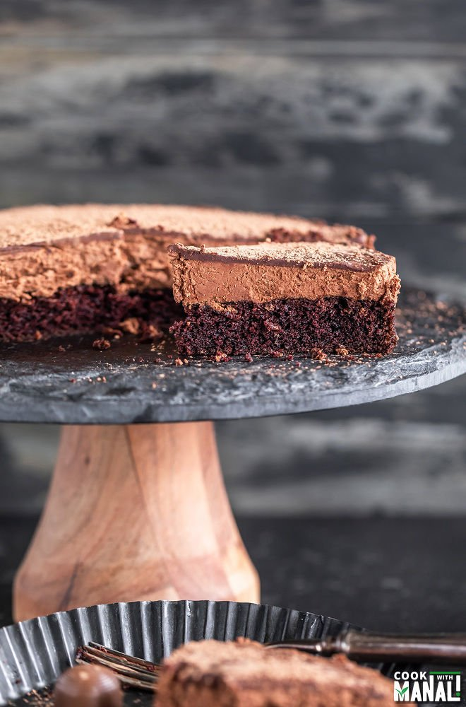 slice of eggless chocolate mousse cake placed on a black cake stand with another slice placed in a plate