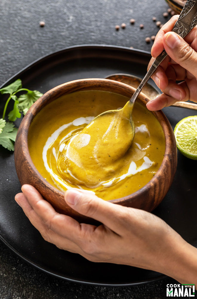 pair of hands holding a wooden bowl full of soup with one hand holding a spoon into the bowl