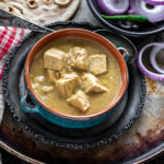 creamy shahi tofu curry served in a blue bowl with sliced red onion rings on one side and tandoori roti placed in the background
