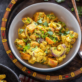 bowl of yellow color salad with cauliflower, sweet potato, onions and garnished with cilantro placed in a handcrafted serving tray