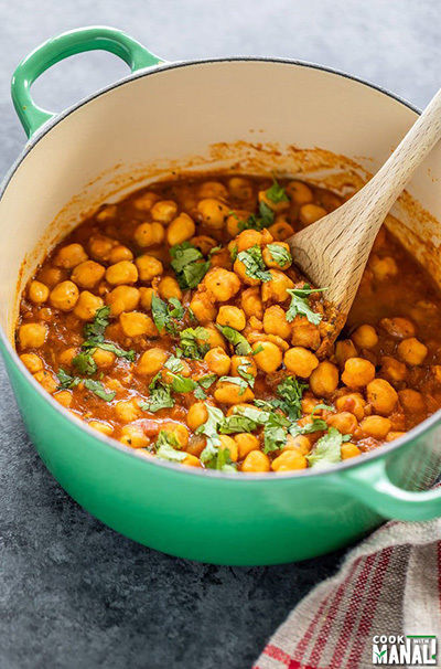 chana masala in a green pot with a wooden spatula