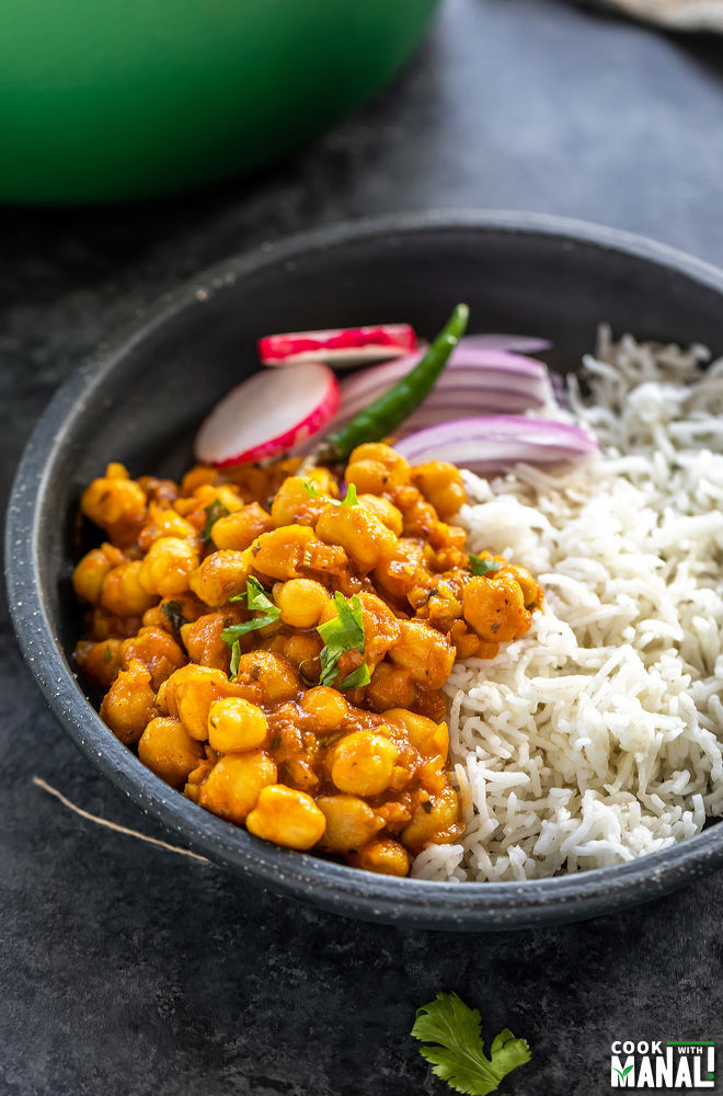 chana masala served with white basmati rice and sliced onions in a black color round bowl