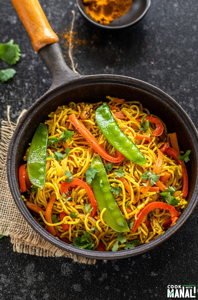 noodles with vegetables in a cast iron pan with bowl of curry powder placed on one side in the background