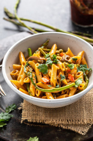 bowl of pasta with asparagus, peppers and topped with cilantro with few more asparagus placed in the background
