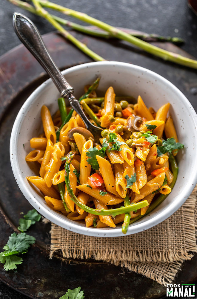 bowl of pasta with veggies like asparagus and garnished with cilantro with a spoon placed on one side