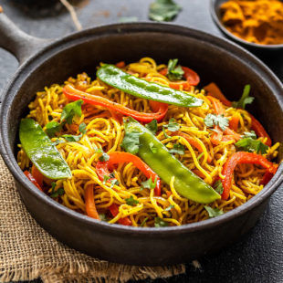 noodles with peppers, snow peas served in a black cast iron pan with a bowl of curry powder in the background along with two golden spoons