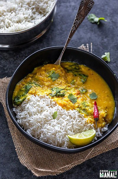 rice and dal in a black bowl, garnished with cilantro and a spoon placed on the side