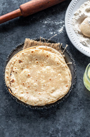 stack of roti placed in a silver antique looking plate with a rolling pin placed in the background and plate of wheat flour on the side