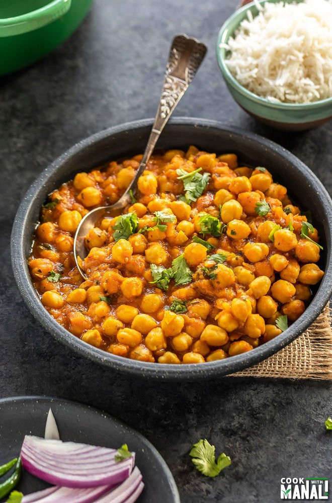 chana masala served in a round black bowl with a spoon, a small bowl of rice placed in the background and another plate with sliced onions on the side