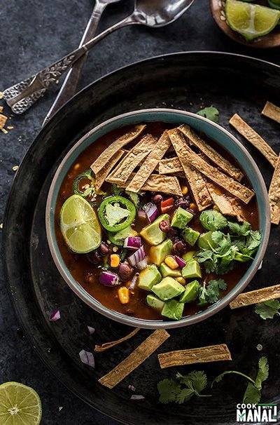 bowl of tortilla soup garnished with tortilla chips, cilantro, avocado, jalapeno