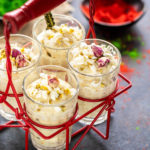 four glasses of white chocolate thandai mousse placed in a glass holder with bowls filled with red and green color in the background