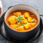 curry of potatoes, paneer and peas served in a black bowl and garnished with cilantro
